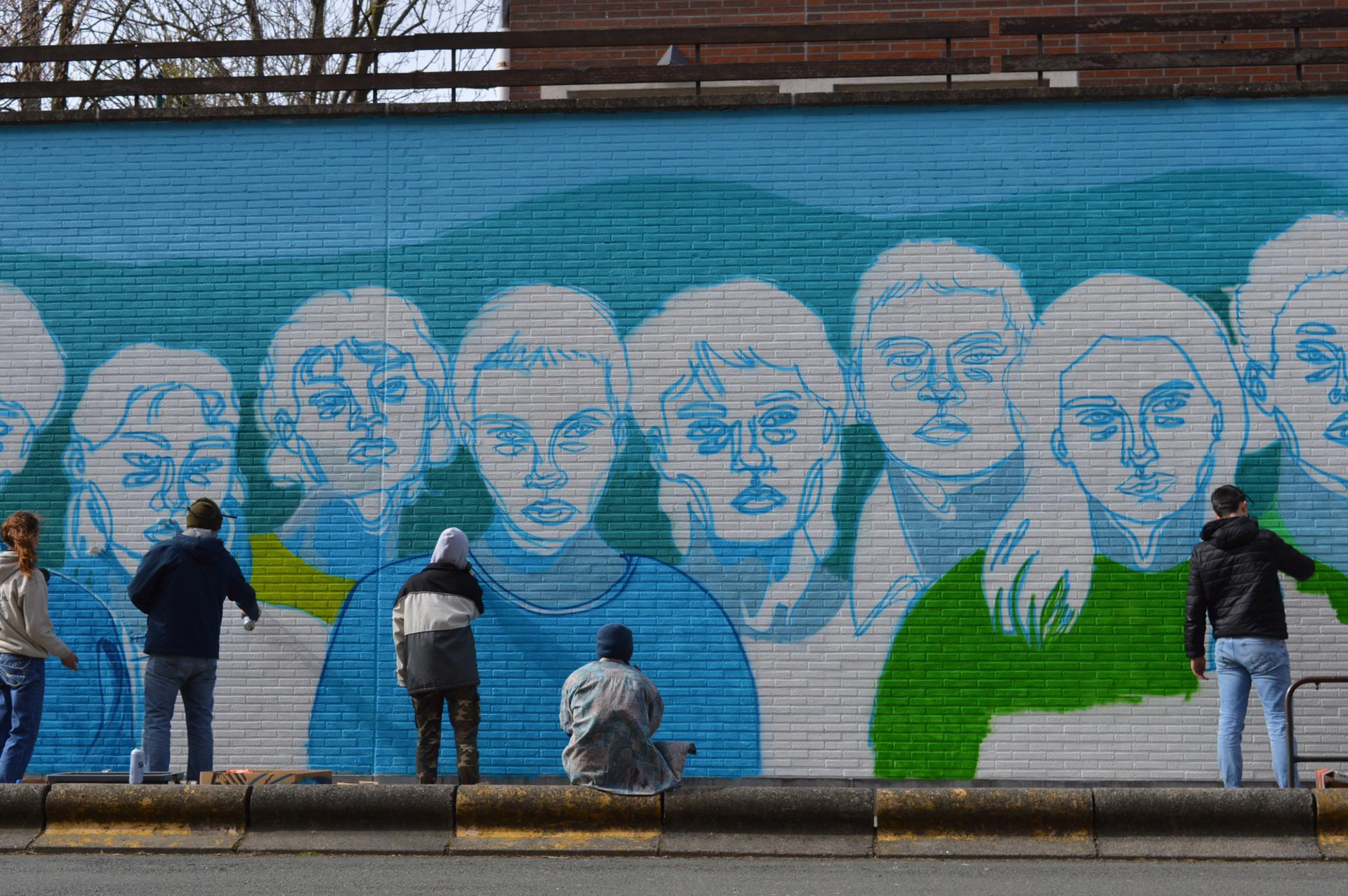 People standing in front of a wall with graffiti Description automatically generated with low confidence